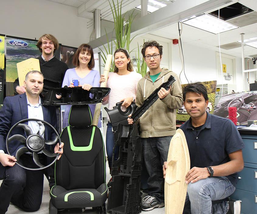 福特汽车公司研究团队的一些成员目前正在研究涉及生物聚合物、天然纤维增强材料的新应用,并为以前被当作废物的材料带来了新的生命。左起:首席研究科学家Alper Kiziltas博士举着一个采用玻纤增强PCR PP、PA6/6制成的风扇,他蹲在一个覆盖着生物基PET织物的座椅旁边;研究工程师Dan Frantz举着一个用于座椅缓冲的大豆基聚氨酯泡沫块;高级技术负责人Debbie Mielewski博士举着咖啡渣以及由碳化咖啡渣填充的PP成型出的前照灯外壳;研究工程师Cindy Barrera-Martinez博士举着一个竹竿和一个含有回收轮胎橡胶的生物基聚氨酯发动机罩,她站在一个由纤维素/LFT混合复合材料制成的控制台基板后面;博士后研究员Sandeep Tamrakar博士握着一个纤维素/LFT混合复合材料制成的门槛护板;博士实习生Golam Rasul博士握着一个红麻纤维增强PP制成的门垫(图片来自福特汽车公司)